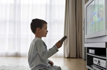 Boy sitting on floor watching cartoons on television