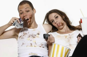 Man and woman eating while watching television on couch