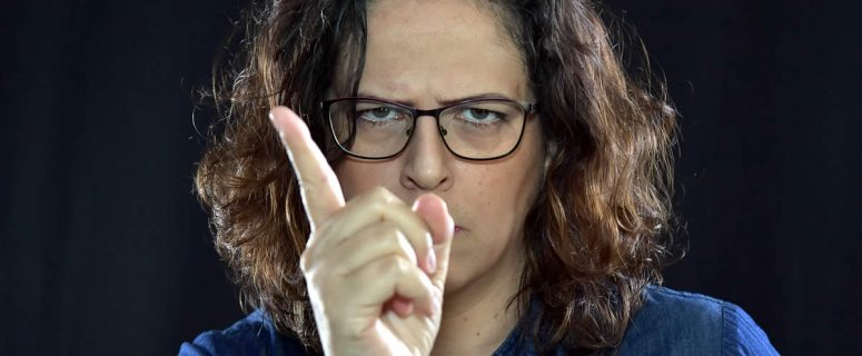 Angry woman in glasses with warning finger